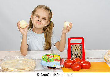Six year old girl at the kitchen table having fun holding vegetables