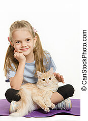 Six year old girl athlete sitting on a rug with cat on her lap