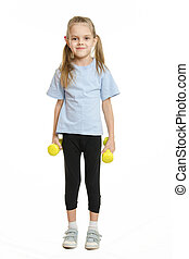 Six year old girl athlete standing with dumbbells
