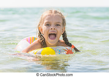 Six year old girl bathing in the sea with his mouth open in pleasure