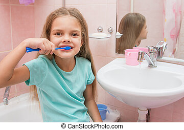 Six year old girl brushing her teeth and turned away from the sink looks in the picture