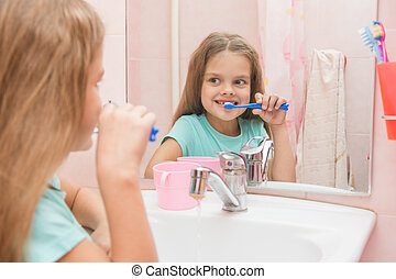 Six year old girl brushing the front teeth look in the mirror in the bathroom