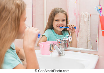 Six year old girl brushing the front teeth with a smile and looked into the frame