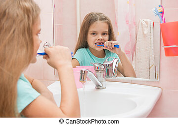 Six year old girl cleans teeth side looking in the mirror in the bathroom