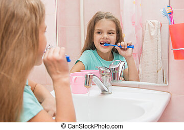 Six year old girl cleans the lower front teeth look in the mirror in the bathroom
