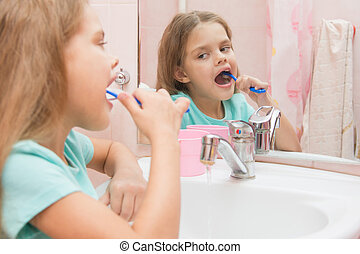 Six year old girl cleans the lower lateral teeth look in the mirror in the bathroom