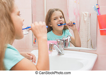 Six year old girl cleans the upper lateral teeth look in the mirror in the bathroom