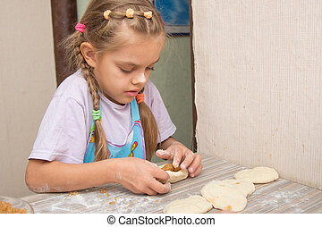 Six year old girl concentrating sculpts cakes with cabbage