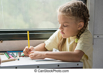 Six year old girl draws pencils in second-class train carriage