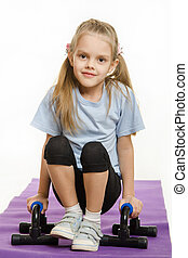 Six year old girl hanging on the palm pushups