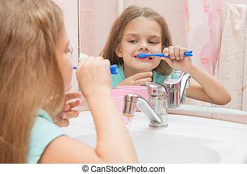 Six year old girl having fun brushing his teeth look in the mirror in the bathroom