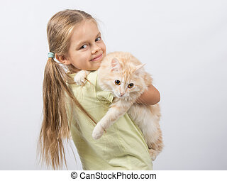 Six year old girl holding a cat in her arms
