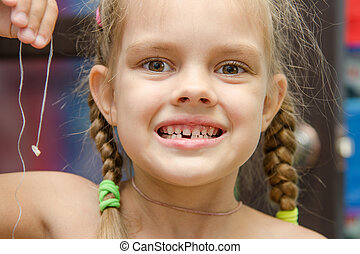 Six year old girl holding her lost tooth on a string