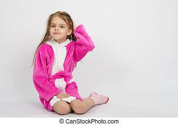 Six year old girl in a bathrobe straightens hair