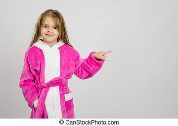 Six year old girl in bathrobe pointing at empty space