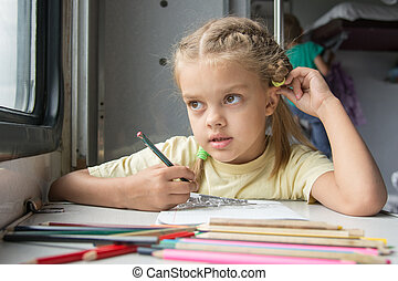 Six year old girl lost in thought looked out the window drawing pencils in second-class train carriage