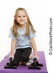 Six year old girl on a rug with stops for push-ups