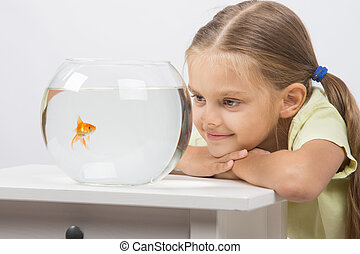 Six year old girl put her head on the handle and looks at a goldfish in an aquarium