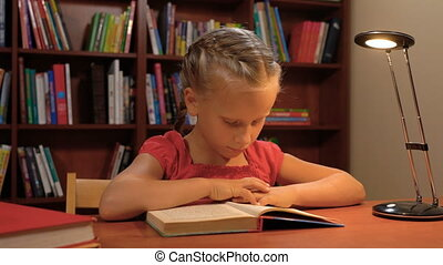 six year old girl reading sitting at the table by the light of a desk lamp