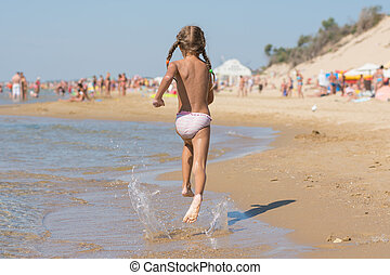 Six year old girl running on the beach