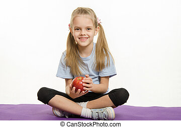 Six year old girl sitting on a rug with an apple hands