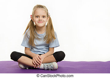 Six year old girl sitting on the mat for practice