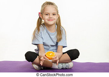 Six year old girl sitting with orange on sport mat