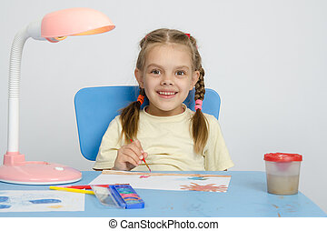 Six year old girl smiling happily, drawing the table