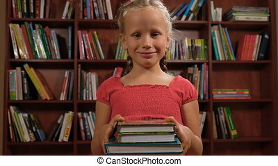 six year old girl standing with books and smiling