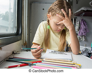 Six year old girl thoughtfully draws pencils in second-class train carriage