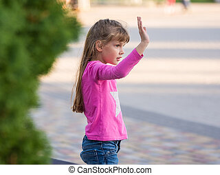 Six-year-old girl waving his hand, side view
