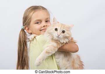 Six year old girl with a cat in her arms
