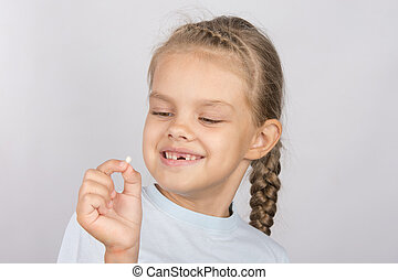 Six year old girl with a smile looking at the fallen baby tooth