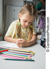 Six year old girl with enthusiasm draws pencils in second-class train carriage
