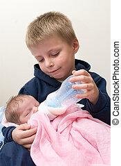 Six year old sibling feeding his newborn baby sister.