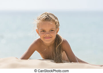 Six-year Tanned girl lying on sand, leaning on hands against the sea