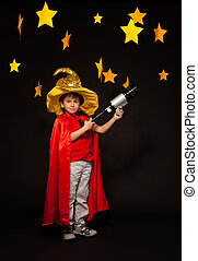 Six years old boy playing stargazer with telescope