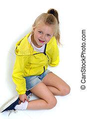 Six years old girl sitting on floor on her knees