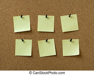 six yellow notes pinned to cork background