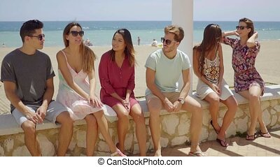 Six young students sitting chatting on a wall with a beach...
