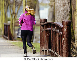 Sized woman jogging in spring park