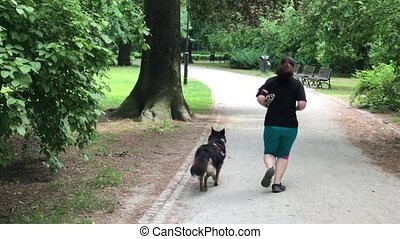 sized woman running with her dog in the park