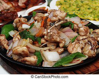 Sizzling bullfrog with vegetables served on iron plate