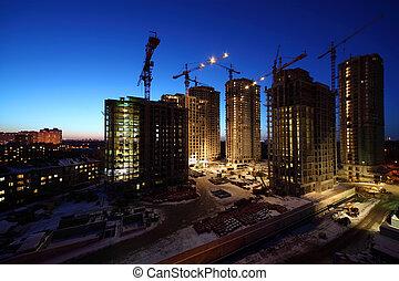sju, hög, bebyggelse, konstruktion under, med, lyftkranar, och, belysning, om natten