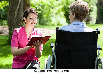 sköta, läsning, bredvid, avstängd kvinna