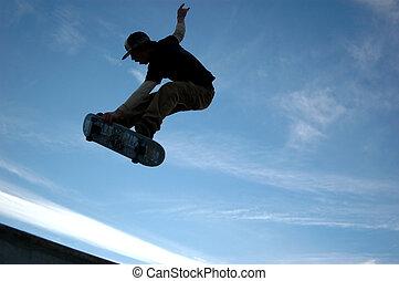 sk8tr air - shilouette of skateboarding male against blue ...