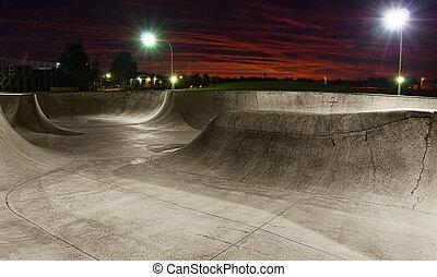 Skate Park - A skate park at night with lights on and sunset...