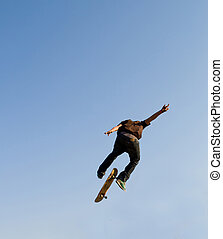 skateboard jump - a boy jumping in the air on skateboard