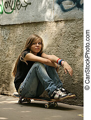 Skateboard - The girl with skateboard sitting against a wall