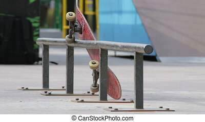 Skateboard with spin wheels lying on the rail in skatepark, close-up view
